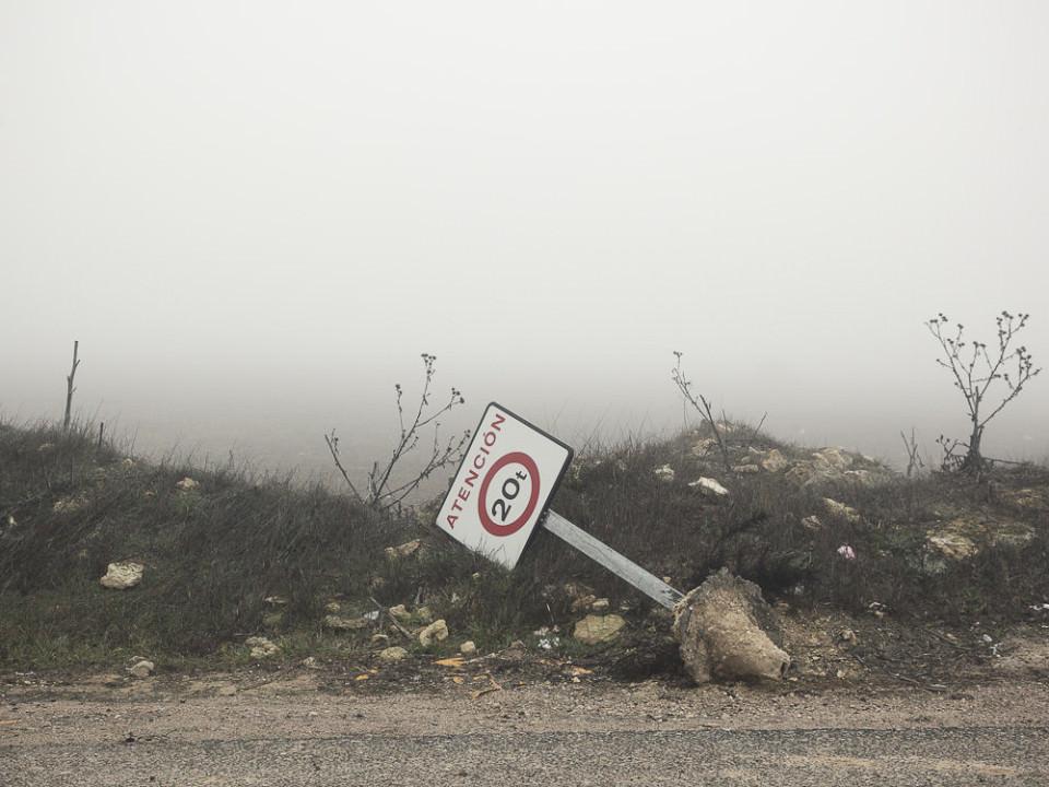 Ein Straßenschild liegt am Straßenrand, dahinter Nebel.