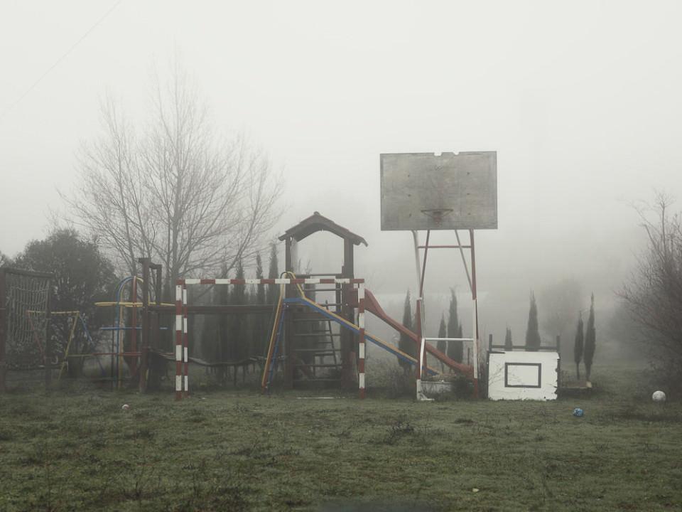 Ein etwas heruntergekommener, leerer Spielplatz auf einer Wiese im Nebel.