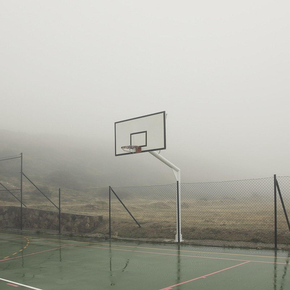 Ein leerer, nasser Basketball-Platz im Nebel.