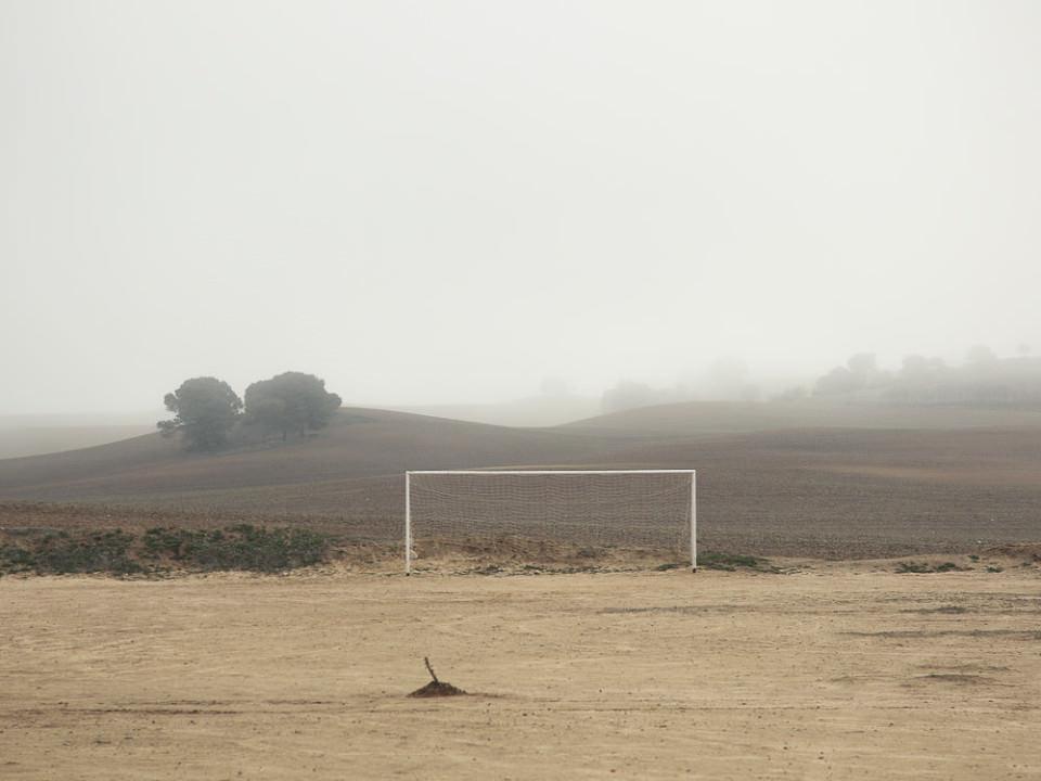 Ein Fußballtor zwischen einem Feld und einer Sandfläche im Nirgendwo vor Nebel.