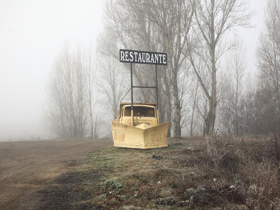 """Ein gelb angemalter, mit einem Schild """"Restaurant"""" versehener Pflug am Feldrand, dahinter Nebel und einige kahle Bäume."""