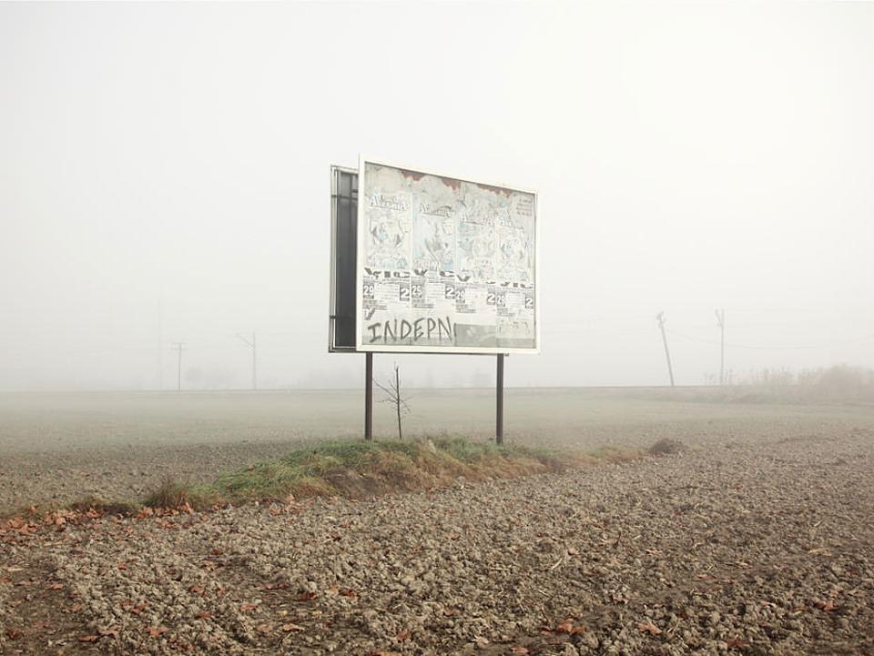 Eine ausgeblichene, mit Graffiti versehene Werbetafel auf einem leeren Feld vor dichtem Nebel.
