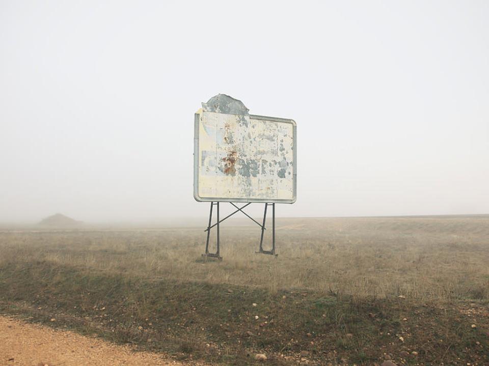 Eine ausgeblicheneWerbetafel auf einem leeren Feld vor dichtem Nebel.