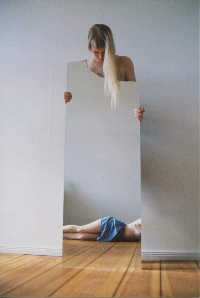 Eine Frau mit einem Spiegel und einer halben Frau darin.