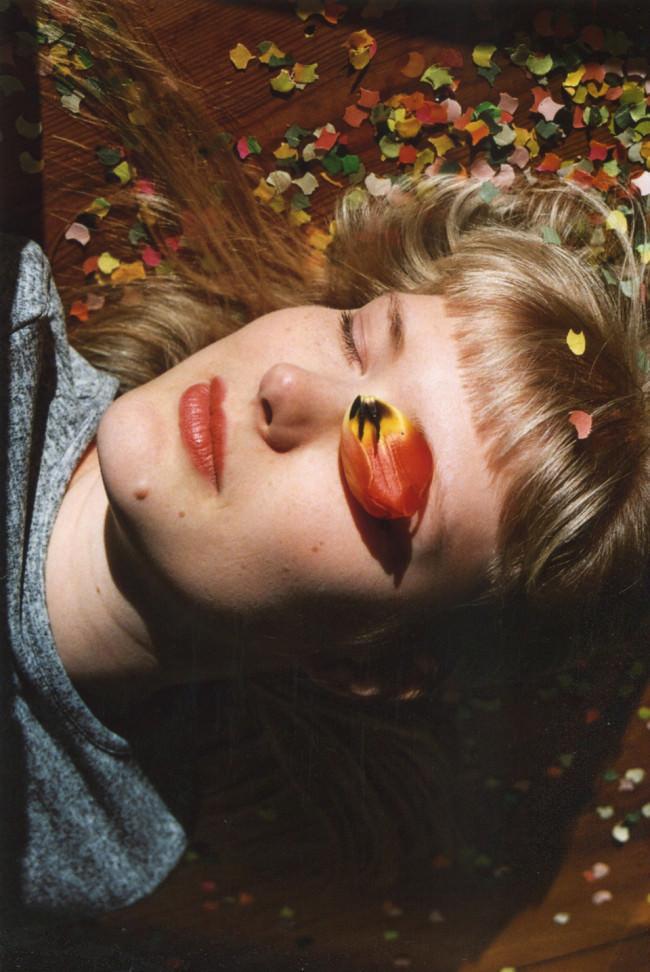 Eine liegende Frau mit blonden Haaren und einem Blütenblatt auf dem Auge.
