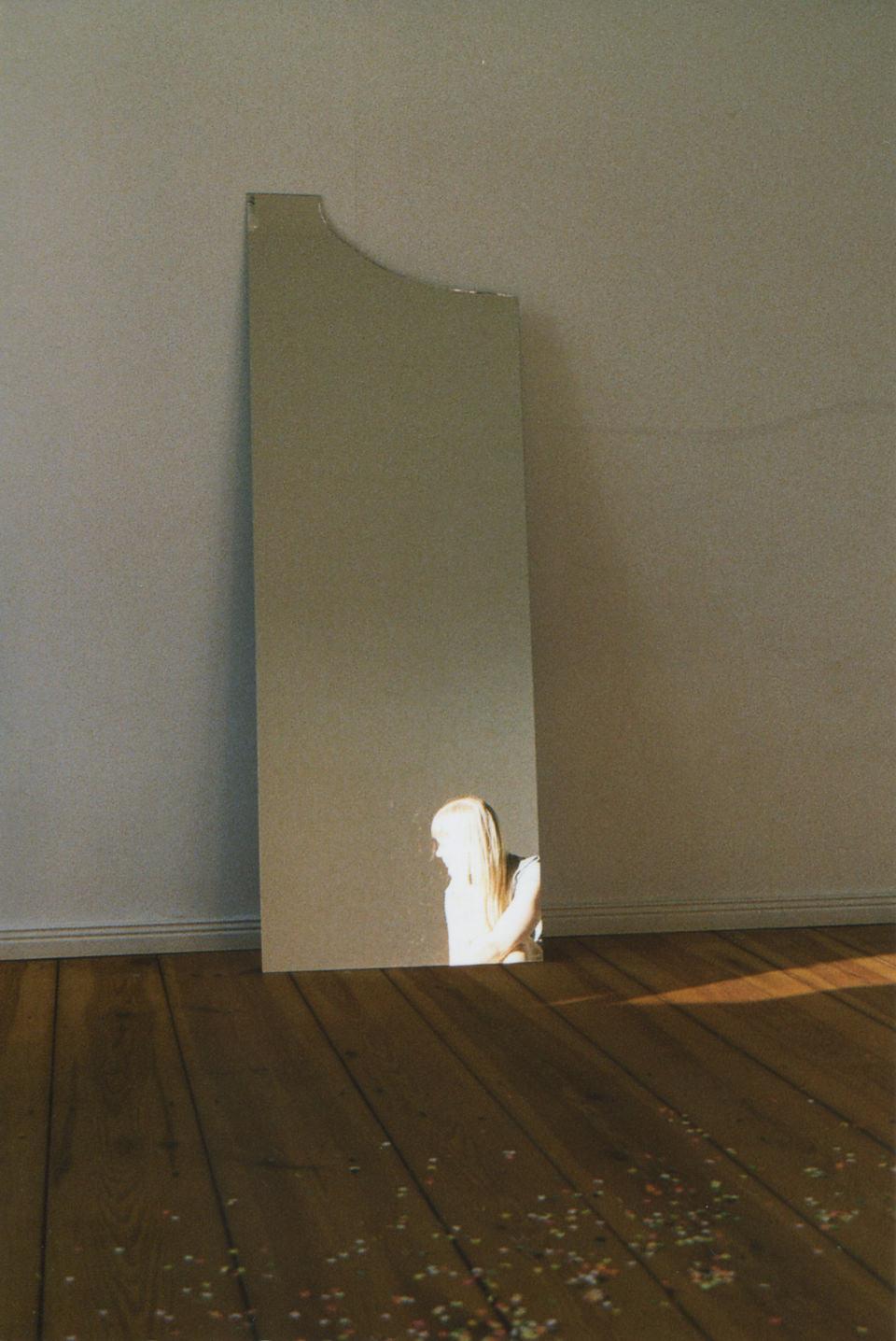 Eine Wand, ein Spiegel und eine recht helle Frau.