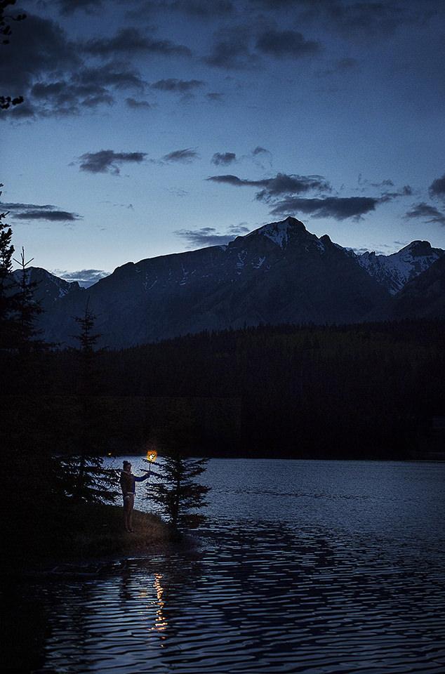 Ein See bei Dämmerung. Eine Person mit Fackel steht am Rand.