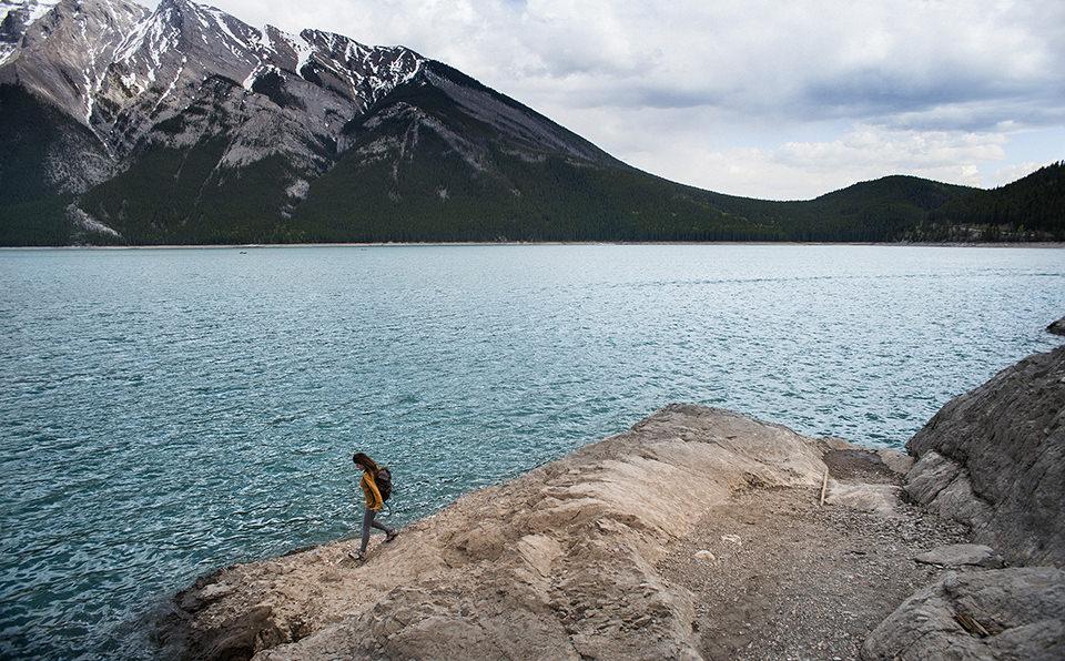 Eine Frau läuft am Rande eines Sees.