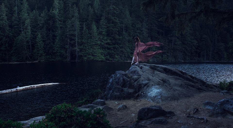 Eine Frau steht mit wehendem Kleid am Rand des Baches.