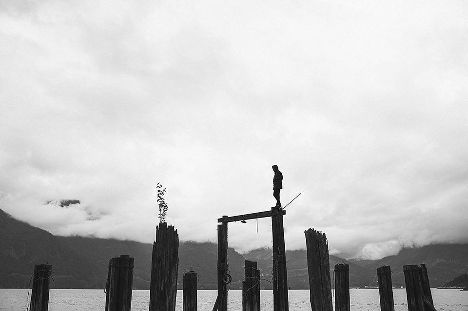 Ein Mann balanciert auf hohen Holzstegen.