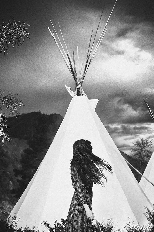 Eine Frau steht im Profil vor einem Tippi. Ihre Haare fliegen im Wind.
