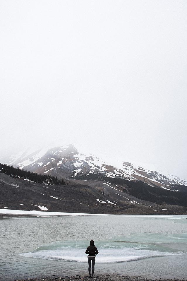 Eine Person steht vor einem See. Im Hintergrund ein Berg.