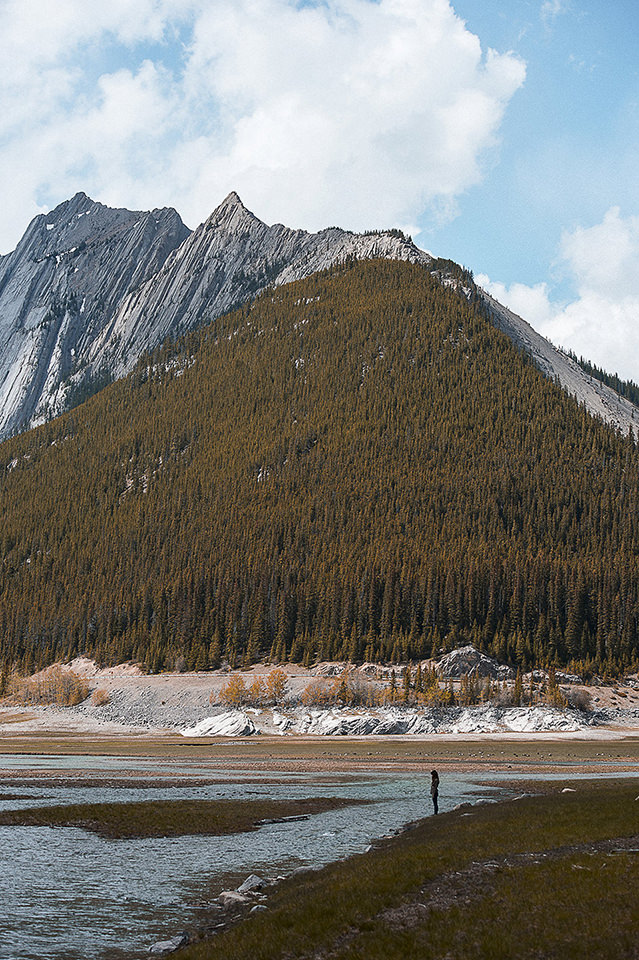 Eine Person am See. Im Hintergrund ein Berg.