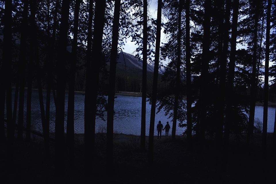 Ein Pärchen steht in der Dämmerung zwischen Bäumen am See.