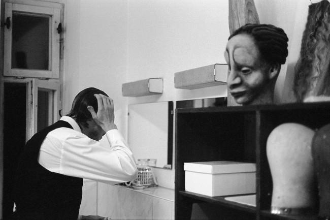 Eine Mann stütz seinen Kopf auf seine Hände und schaut vielleicht in den Spiegel.