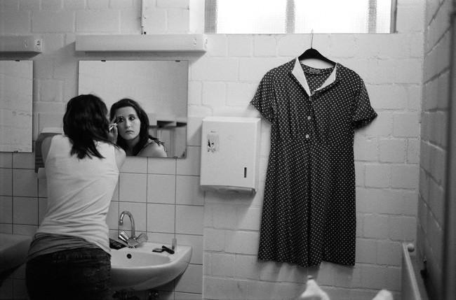 Eine Frau vor einem Spiegel, ein Kleid an der Wand.