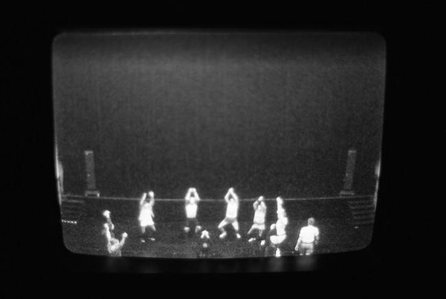 Auf einem Monitor sind eine Reihe von Menschen auf einer Bühne zu sehen.