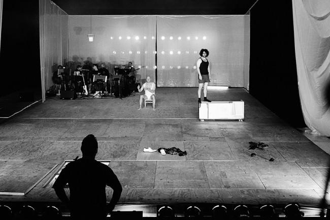 Jemand schaut auf die Bühne, jemand steht auf der Bühne, beide schauen sich an.