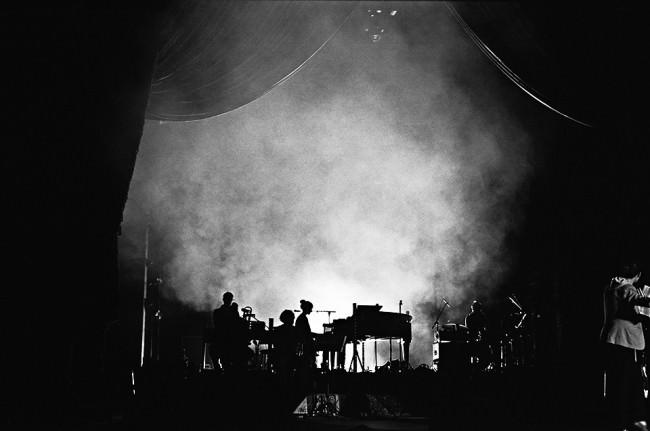 Blick auf die Bühne im Gegenlicht mit viel Rauch und einem Klavier sowie Menschen.