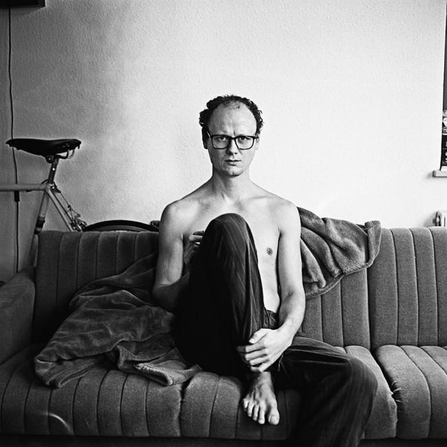 Ein Mann mit Brille sitzt auf einer Couch.