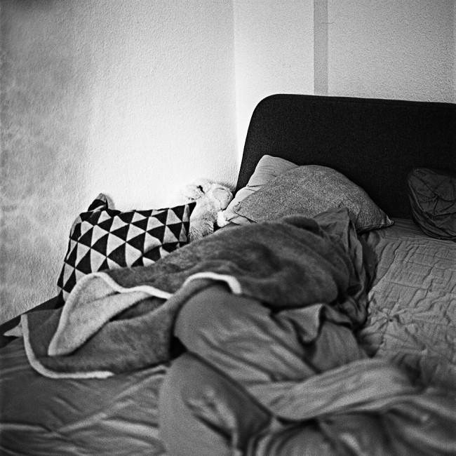 Man sieht auf ein ungemachtes Bett.