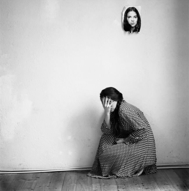 Eine Frau hockt auf dem Boden und versteckt ihr Gesicht. An der Wand hängt ein Bild von ihr.