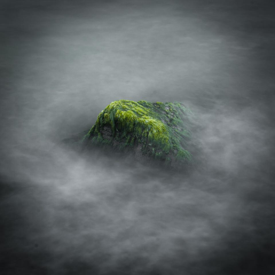 Ein wasserumschlungener Stein, der von Moos überzogen ist. Eine Langzeitbelichtung.