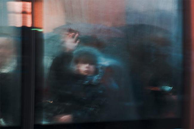 Verwischtes Bild eines Kindes hinter einer Scheibe bei Regen