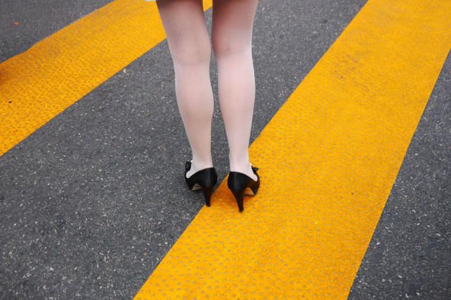 Frauenbeine in Strumpfhose und Pumps auf gelben Straßenmarkierungen