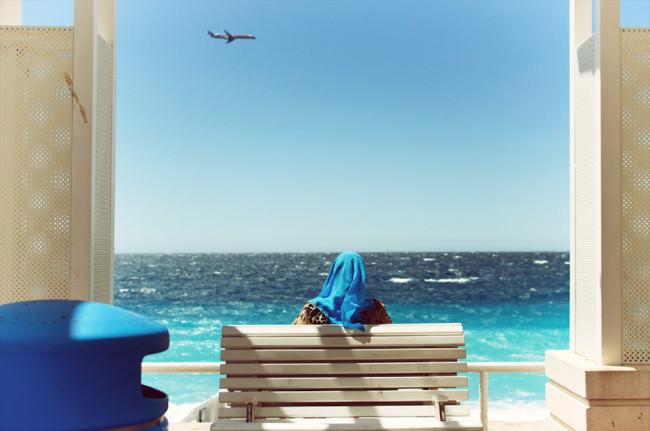 Frau mit blauem Kopftuch vor blauem Wasser, blauem Himmel mit Flugzeug und neben einem blauen Mülleimer.