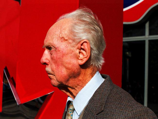 Mann mit roter Haut vor rotem Hintergrund.