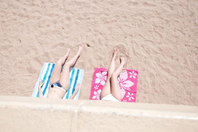 Die Beine von zwei Frauen auf bunten Handtüchern am Strand.