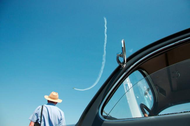 Auto mit halb geöffnetem Fenster, daneben ein Mann mit Hut und am Himmel die Spur eines Flugzeugs.