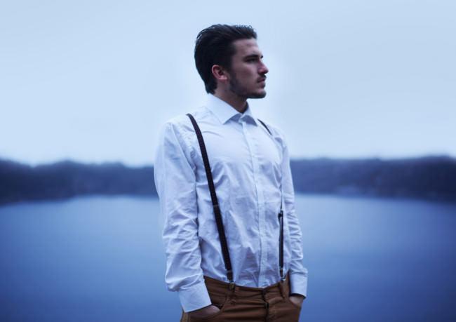 Junger Mann in weißem Hemd vor blauer Abendlandschaft