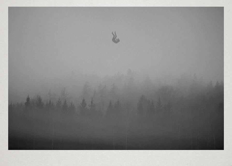 Eine Person fällt über einem Wald vom Himmel.