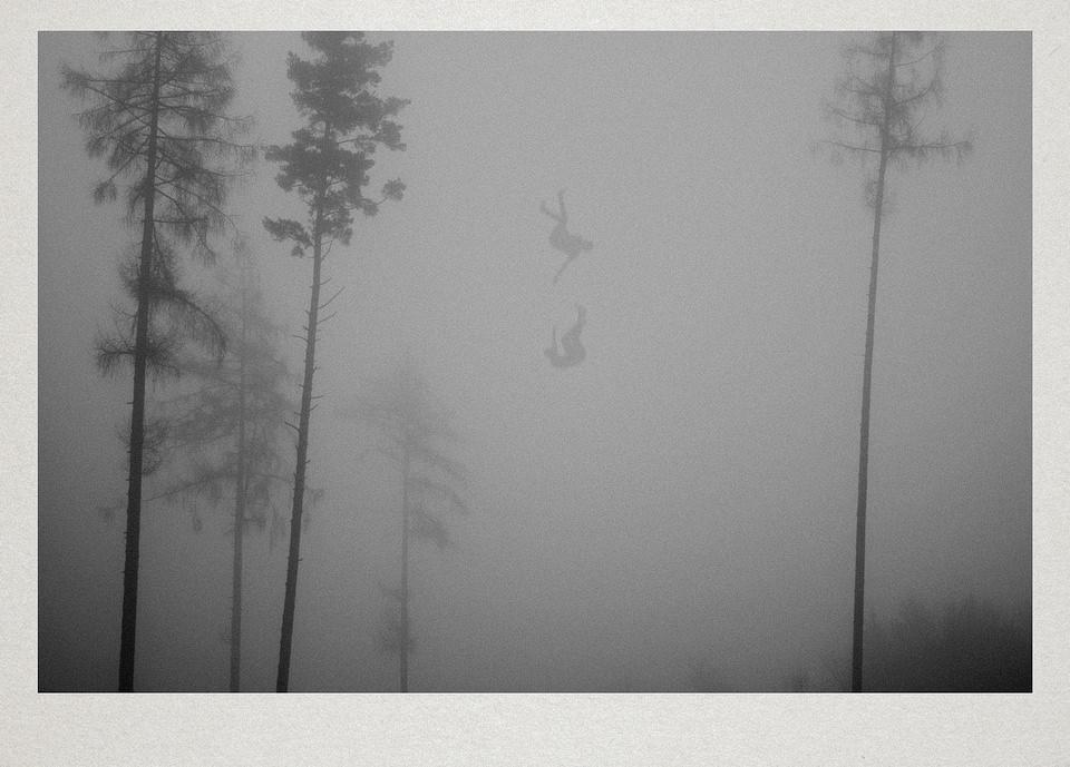 Zwei Personen fallen im Nebel zwischen Bäumen vom Himmel.