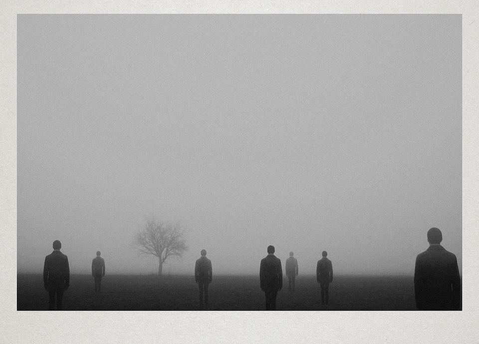 Einige Menschen und ein Baum stehen auf einem nebligen Feld.