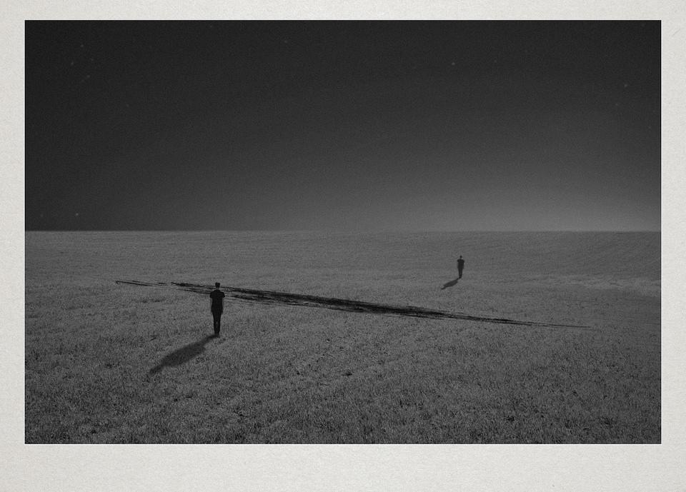 Zwei Personen stehen auf einem Feld, zwischen ihnen liegt ein Schatten.