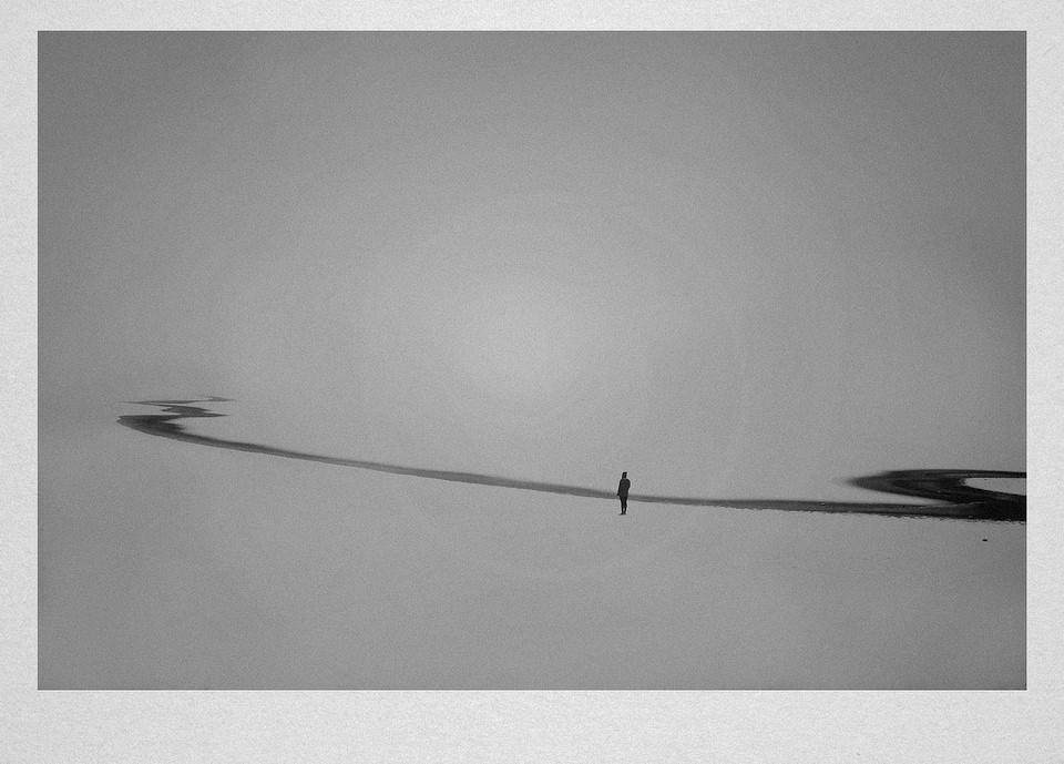 Eine Person steht in einer verschneiten Landschaft an einem Fluss.