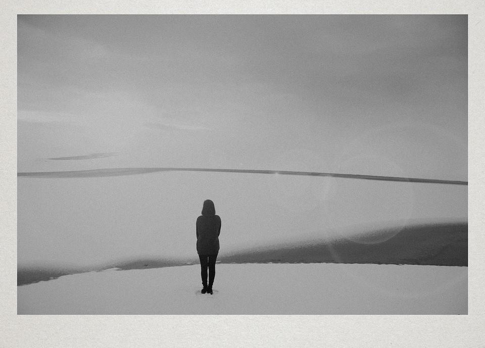 Eine Person schaut auf eine fast abstrakte Schneelandschaft.