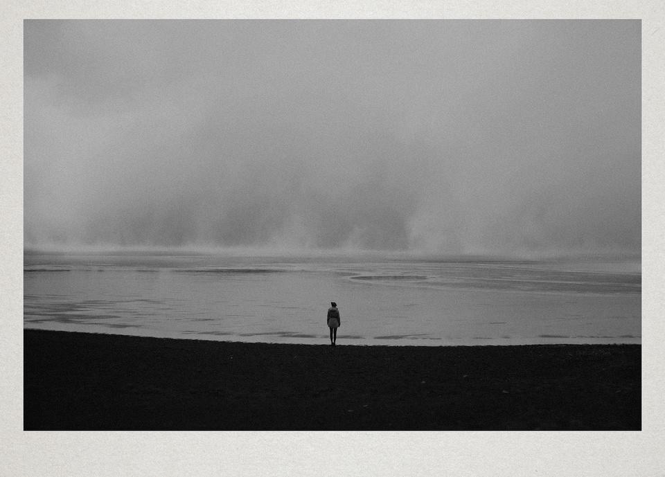 Eine Person steht am Strand.