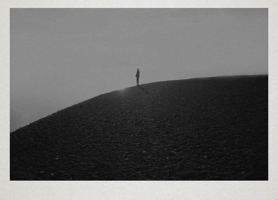 Eine Person steht auf einem Hügel.