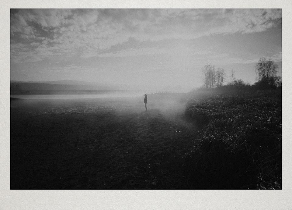 Eine Person steht in einer nebligen Landschaft.