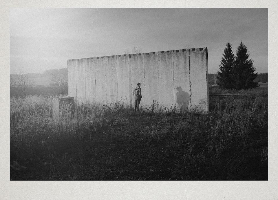 Eine Person steht vor einer Betonwand in der Natur.