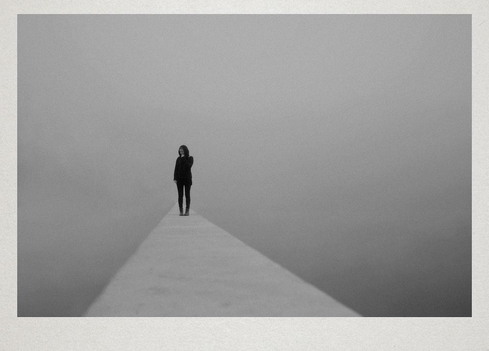 Eine Person steht auf einem Steg im Nebel.