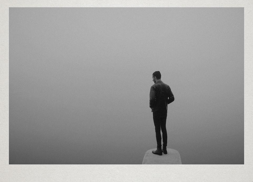 Eine Person steht am Ende eines Steges im Nebel.