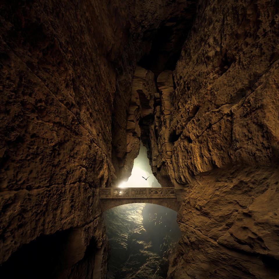 Eine Spalte in einer Felshöhle wird von einer Brücke überspannt, über die ein Vogel fliegt.
