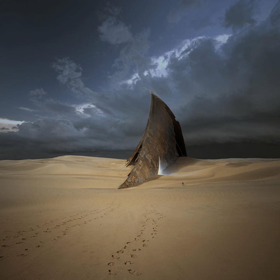 Ein metallisches Gebäude in Form einer großen Flosse, aus der blaues Licht strahlt, ragt aus einer Wüstenlandschaft auf.