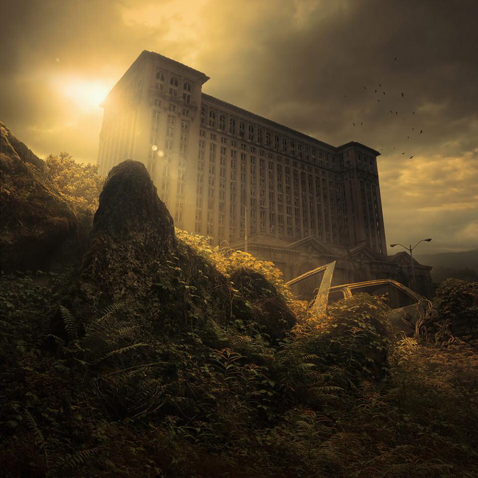 Hinter Felsen und von Pflanzen überwucherten Autowracks ragt ein hohes Gebäude auf.