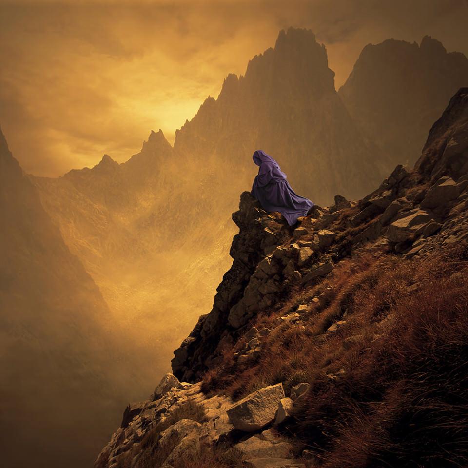 Auf einem Felsvorsprung an einem Hang sitzt eine violett gewandete Person, im Hintergrund eine Gebirgslandschaft.